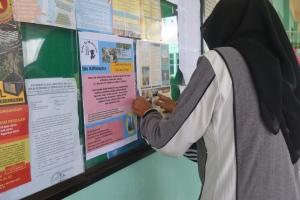 Poster Edu AtMalaysia sedang ditampal di majalah dinding SMAN 1 Bintan Timur